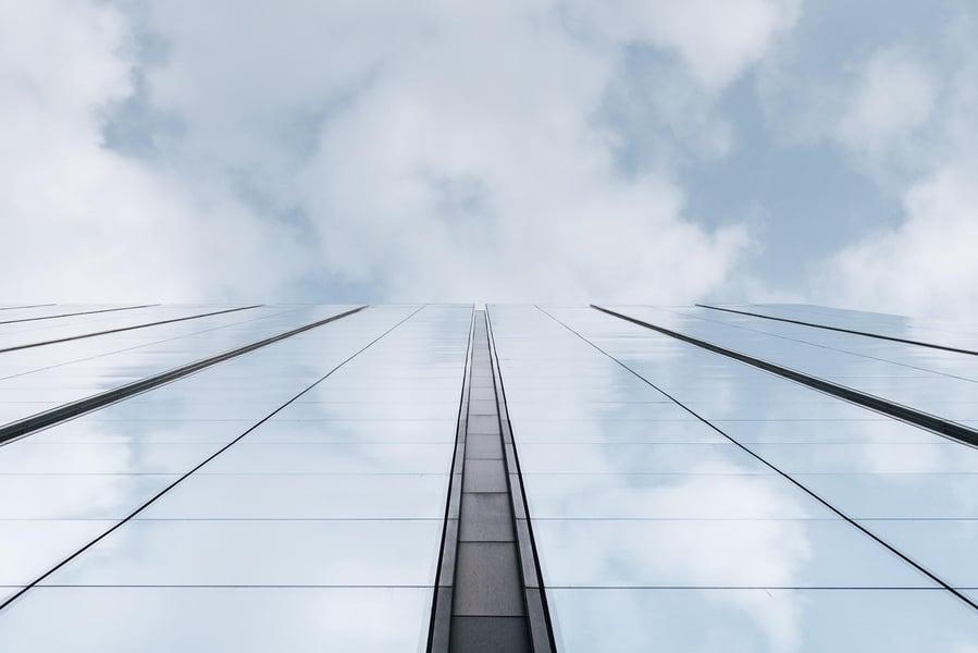 Firmengebäude vor Wolken am Himmel, sinnbildlich für Cloud Transformation in Unternehmen